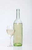 Botella del vino blanco con el vidrio medio lleno Foto de archivo