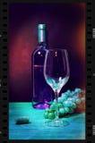Botella del vino blanco en marco de película de tira con el vidrio y el manojo de uvas en la tabla de madera Fotos de archivo libres de regalías