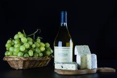Botella del vino blanco, queso verde y un manojo de uvas maduras en un fondo negro Foto de archivo libre de regalías