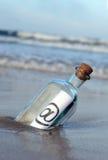 Botella en la playa, @, email Foto de archivo