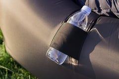 Botella en un bolsillo inflable del sofá Imágenes de archivo libres de regalías