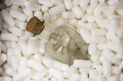 Botella frágil en pelotillas de la espuma fotografía de archivo