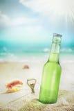 Botella helada de cerveza dorada o de soda en una playa Foto de archivo libre de regalías