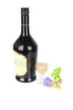 Botella negra del licor con dos dulces. Imagenes de archivo