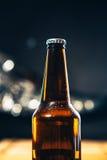 Botella oscura de cerveza en un fondo borroso foto de archivo