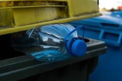 Botella plástica azul grande en un cubo de la basura verde amarillo - recicle para la naturaleza foto de archivo libre de regalías