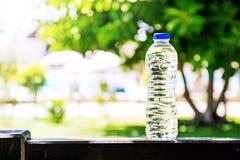 Botella plástica con agua que se coloca en un verano, árboles y piscina en un fondo Imágenes de archivo libres de regalías