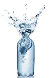 Botella plástica con el chapoteo del agua aislado imagen de archivo