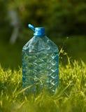 Botella plástica de agua en la hierba Fotos de archivo libres de regalías