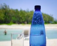 Botella plástica de agua en la playa Imagenes de archivo