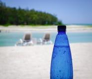 Botella plástica de agua en la playa Imagen de archivo