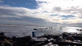 Botella plástica en la arena mojada lanzada hacia fuera por la onda del mar almacen de metraje de vídeo