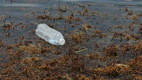 Botella plástica que flota en el océano almacen de video