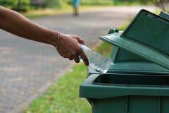 Botella que lanza de la mano en botes de basura Imágenes de archivo libres de regalías