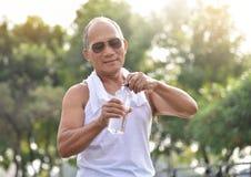 Botella que se sostiene masculina mayor asiática de agua Fotos de archivo