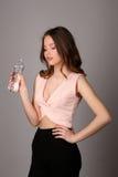 Botella que se sostiene modelo de agua Cierre para arriba Fondo gris Fotografía de archivo libre de regalías