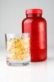 Botella roja con las cápsulas del petróleo en la taza de cristal Fotos de archivo