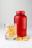 Botella roja con las cápsulas del petróleo en la taza de cristal Fotografía de archivo libre de regalías