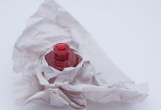 Botella roja y papel arrugado Foto de archivo