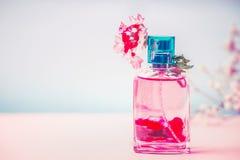 Botella rosada de perfume con las flores, el producto cosmético natural o el concepto de la belleza en fondo azul en colores past fotografía de archivo libre de regalías