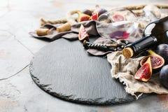 Botella, sacacorchos, vidrio del vino rojo, higos en una tabla Imágenes de archivo libres de regalías