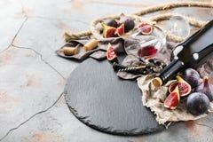 Botella, sacacorchos, vidrio del vino rojo, higos en una tabla Imagenes de archivo