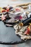 Botella, sacacorchos, vidrio del vino rojo, higos en una tabla Fotos de archivo libres de regalías