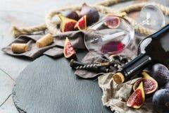 Botella, sacacorchos, vidrio del vino rojo, higos en una tabla Fotografía de archivo libre de regalías