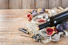Botella, sacacorchos, vidrio del vino rojo, higos en una tabla Fotos de archivo
