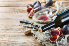 Botella, sacacorchos, vidrio del vino rojo, higos en una tabla Foto de archivo libre de regalías