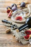 Botella, sacacorchos, vidrio del vino rojo, higos en una tabla Imagen de archivo