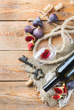 Botella, sacacorchos, vidrio del vino rojo, higos en una tabla Foto de archivo