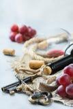 Botella, sacacorchos, vidrio del vino rojo, uvas en una tabla Imagen de archivo libre de regalías