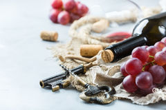 Botella, sacacorchos, vidrio del vino rojo, uvas en una tabla Imágenes de archivo libres de regalías