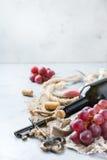 Botella, sacacorchos, vidrio del vino rojo, uvas en una tabla Foto de archivo