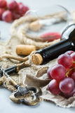 Botella, sacacorchos, vidrio del vino rojo, uvas en una tabla Imagen de archivo
