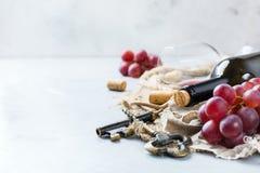 Botella, sacacorchos, vidrio del vino rojo, uvas en una tabla Fotos de archivo