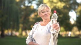 Botella sonriente de la demostración de la mujer de agua chispeante antes de la cámara, forma de vida sana imagen de archivo libre de regalías