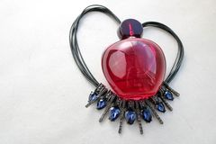 Botella transparente de cristal hermosa roja de perfume femenino que miente en secuencia negra en la forma de un corazón adornado Fotografía de archivo libre de regalías