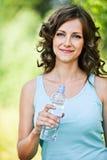 Botella triguena joven de la explotación agrícola de la mujer Foto de archivo libre de regalías