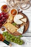 Botella, uva, miel, queso y copa del vino blanco en el tablero de madera blanco fotografía de archivo libre de regalías