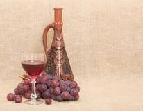 Botella, uvas y vidrio de la arcilla en fondo de la lona Foto de archivo