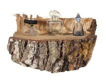 Botella vacía tres de perfume en un pedazo de tronco del abedul Imagenes de archivo