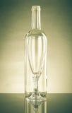 Botella vacía y un vidrio vacío de vidrio claro Con la reflexión Fotografía de archivo