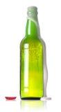 botella verde de cerveza con una espuma que fluye fotos de archivo