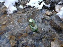 Botella verde quebrada en una corriente de la montaña fotos de archivo libres de regalías
