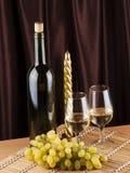 Botella, vidrio con el vino y vela Foto de archivo