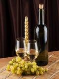 Botella, vidrio con el vino y vela Fotos de archivo