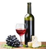Botella, vidrio de vino rojo y uvas maduras Imágenes de archivo libres de regalías