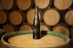 Botella vieja de vino en un barril en sótano del lagar Fotos de archivo